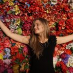 smiling woman laying on colorful flowerbed